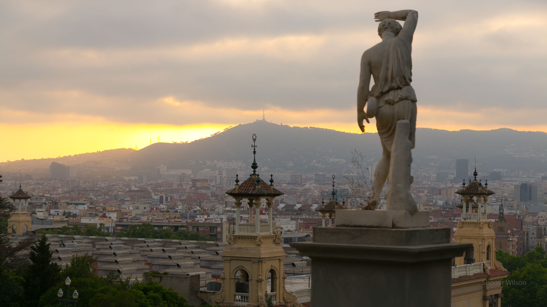 Catalan city skyline from a hillside, with a statue of a person at right, and sunset in the sky