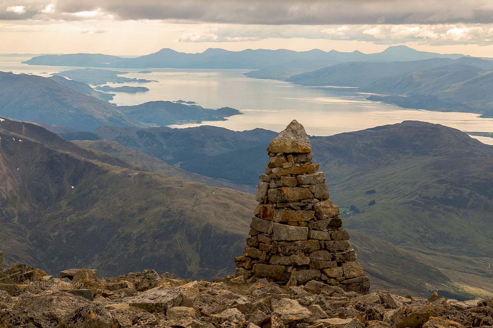 at a high altitude, a cairn of stones surrounded by stones on the ground, with mountains and a sea inlet behind