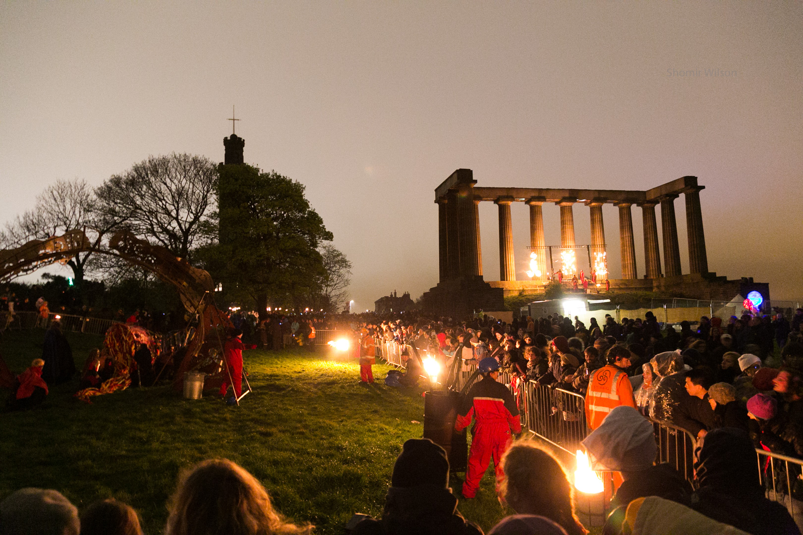 A crowd and event performers with fire at dusk