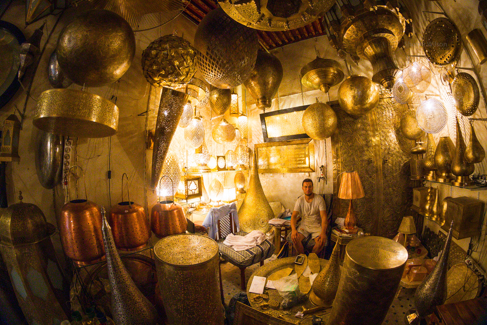 Intricate brass lamps in a lamp shop, with a man sitting in the back