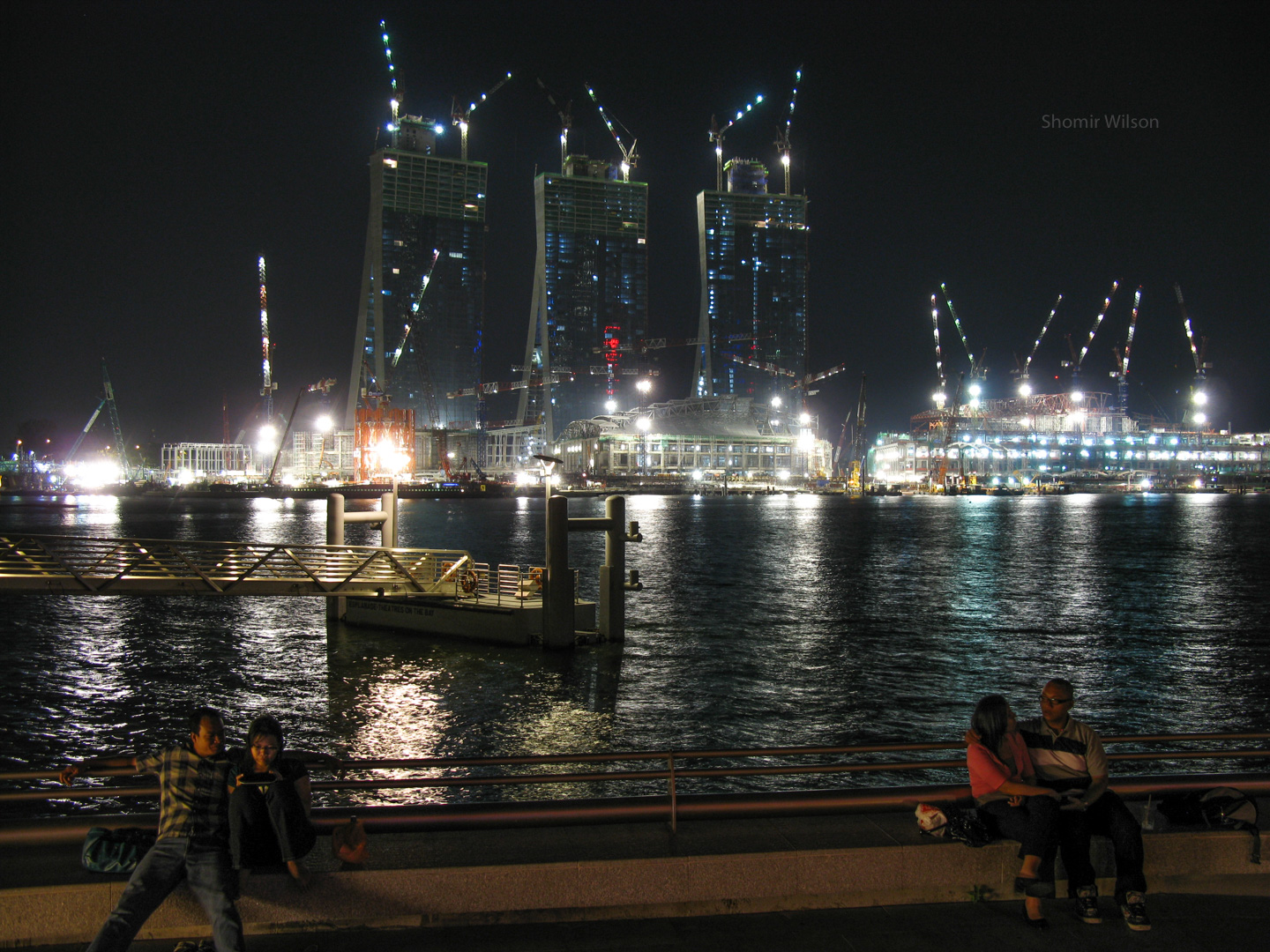 Brightly lit construction site across the water from the foreground, in which two couples canoodle