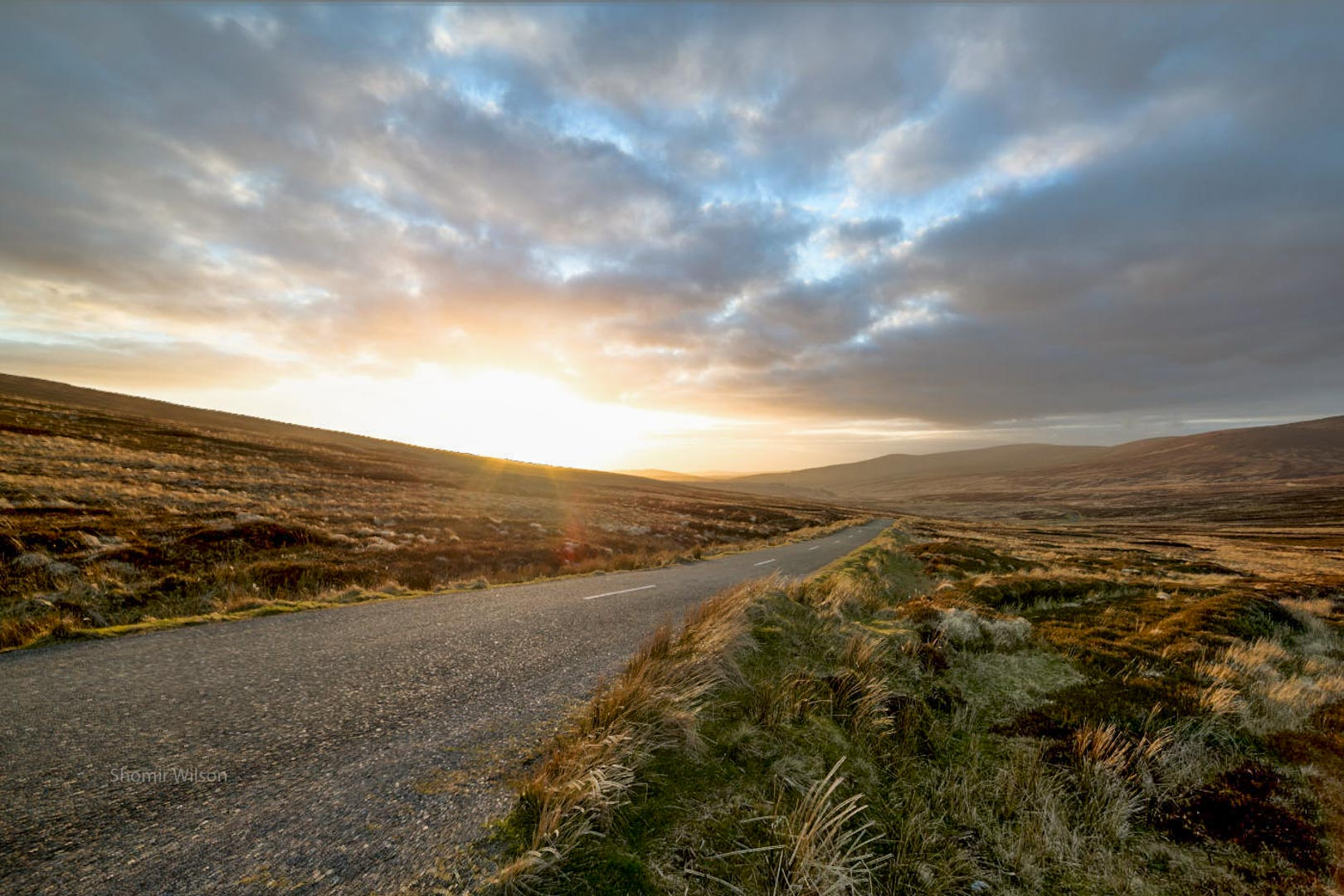road across a boggy plain with with mountains in the distance and a sunset in the sky